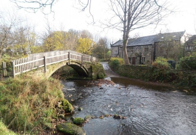 View of Beckfoot Farm and Beckfoot packhorse bridge above the Harden Beck in Bingley
