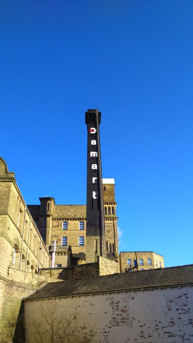 The Damart chimney and tower mill from three rise locks in Bingley