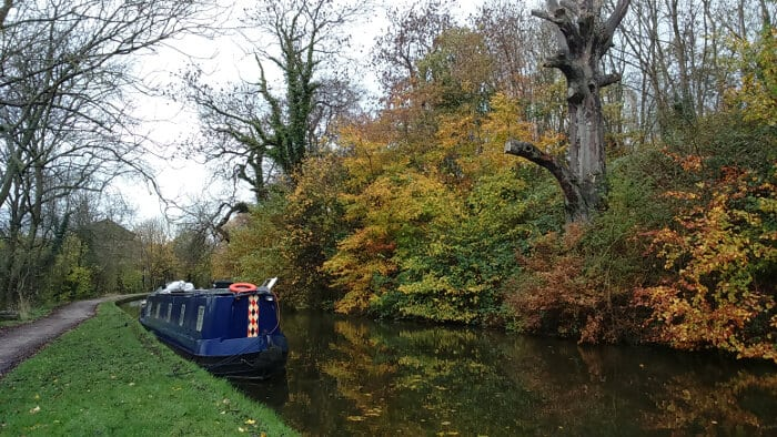 Autumnal view of Leeds and Liverpool canal with barge near Bingley