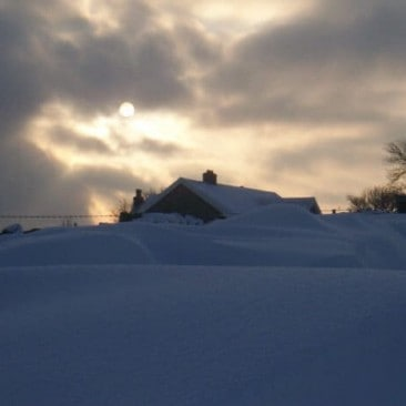 House Covered in Snow with Morning Sunshine
