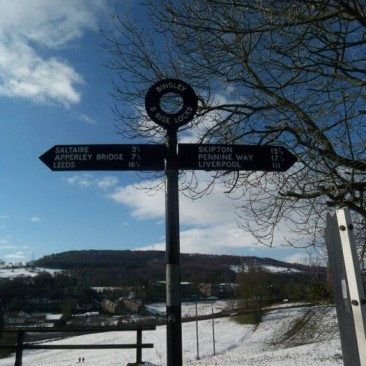 Sign at Bingley Five Rise Locks with field covered in Snow