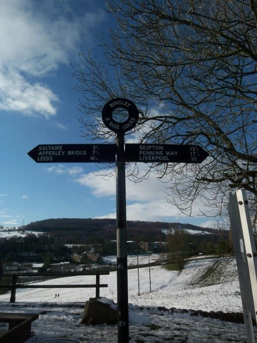 Snow covered field behind sign on top of Five Rise Locks
