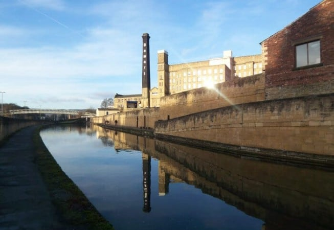 A beam of sunlight reflects from the Damart Mill near Leeds and Liverpool Canal