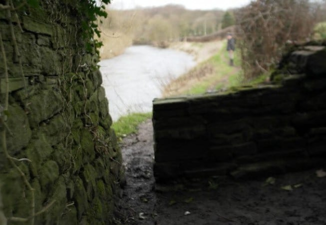 Walker standing on a footpath along the River Aire