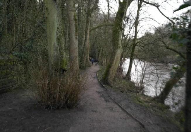 Walkers on riverside footpath in Bingley along River Aire