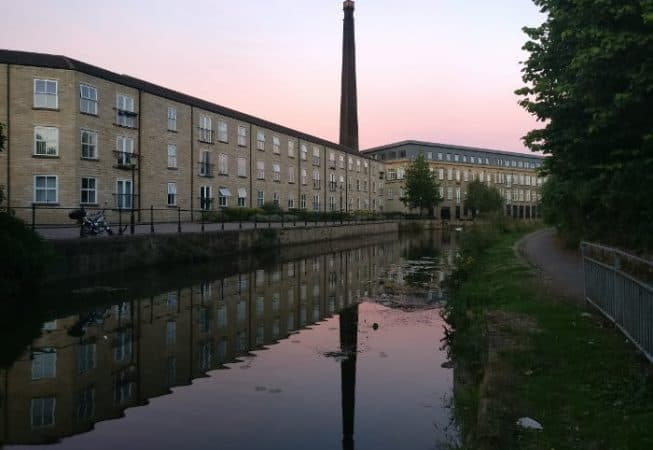 Britannia Wharf Mill being reflected in Leeds and Liverpool Canal with sunset in background